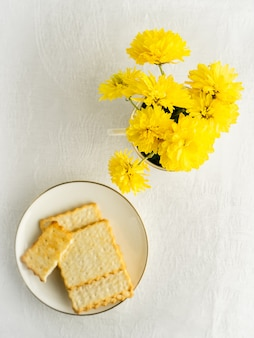 Mazzo dei fiori e dei biscotti gialli della molla sul piatto