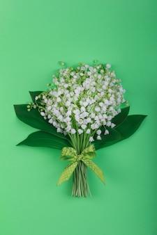 Mazzo dei fiori fragranti del mughetto con le foglie, con un arco verde e bianco del pois su un primo piano verde del fondo