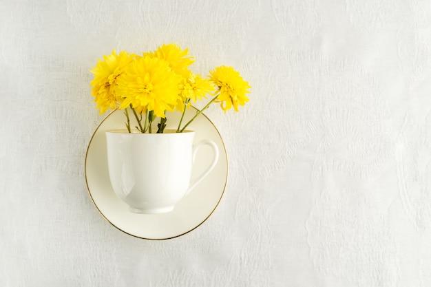Mazzo dei fiori gialli della molla in tazza di tè bianca