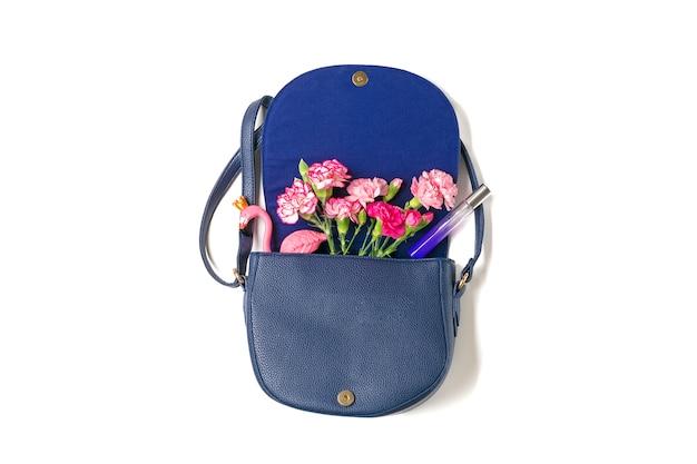 Mazzo dei fiori rosa dei garofani, figura del fenicottero, profumo, borsa della donna isolata su superficie bianca