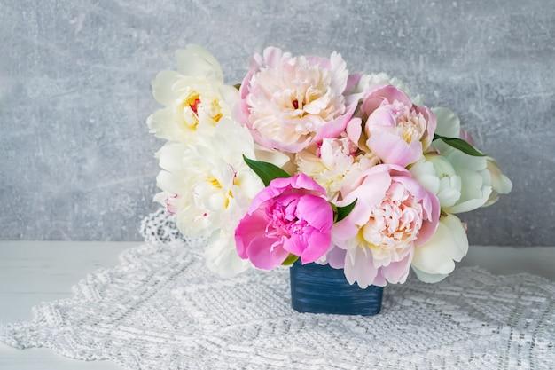 Mazzo dei fiori variopinti della peonia in vaso di fiore blu.