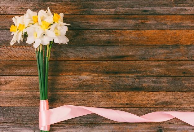 Mazzo dei narcisi con il nastro rosa sul retro lerciume di legno con copyspace