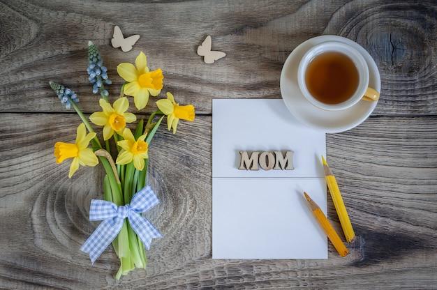 Mazzo dei narcisi e del muscari sulla tavola di legno con la carta, le farfalle e la tazza di tè. biglietto d'auguri. buona festa della mamma. minimalismo, vista dall'alto, posto per il testo.