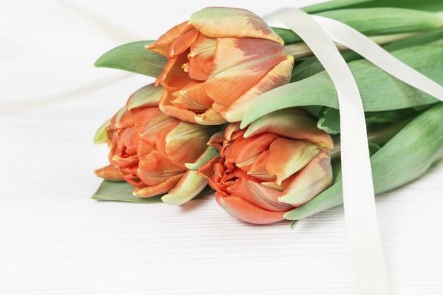 Mazzo dei tulipani arancioni e gialli colorati. sfondo luminoso vacanza con spazio copia per il tuo testo o congratulazioni. biglietto di auguri per la primavera.