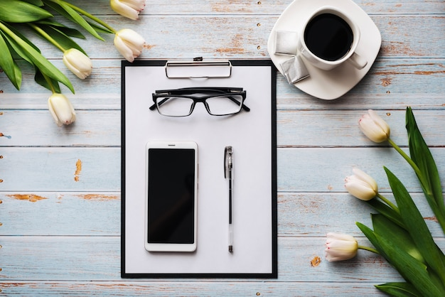 Mazzo dei tulipani bianchi con uno smartphone, una tazza di caffè e una compressa di carta su una tavola di legno