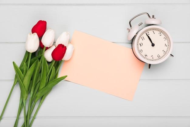 Mazzo dei tulipani con la cartolina d'auguri accanto e l'orologio