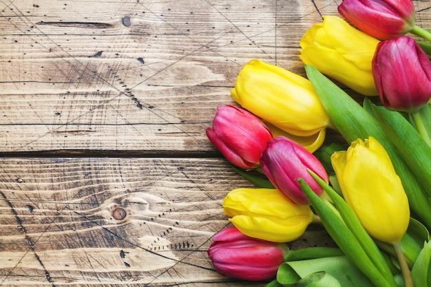 Mazzo dei tulipani gialli e rosa su una superficie di legno