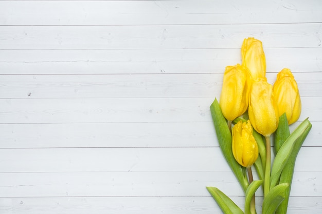 Mazzo dei tulipani gialli luminosi su una tavola leggera