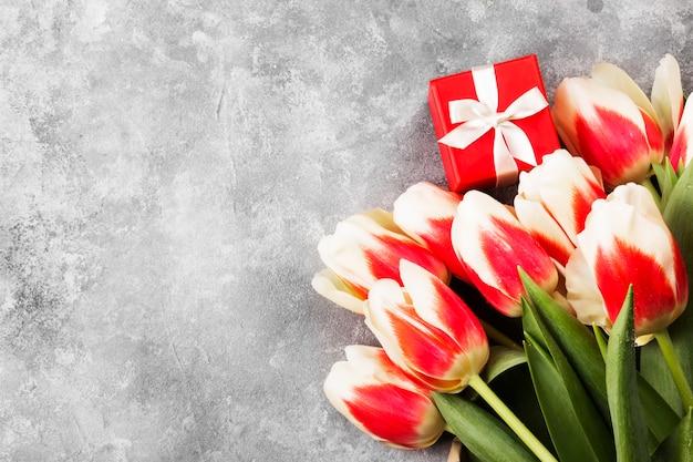 Mazzo dei tulipani rosa bianchi su un fondo grigio. vista dall'alto, copia spazio