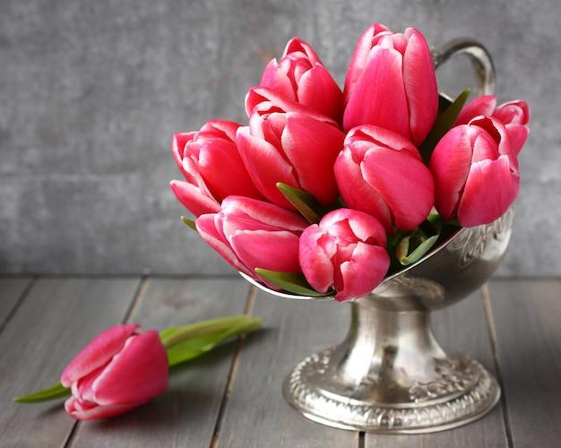 Mazzo dei tulipani rosa in vaso del metallo su fondo di legno