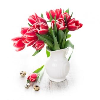 Mazzo dei tulipani rosa in vaso sui precedenti bianchi