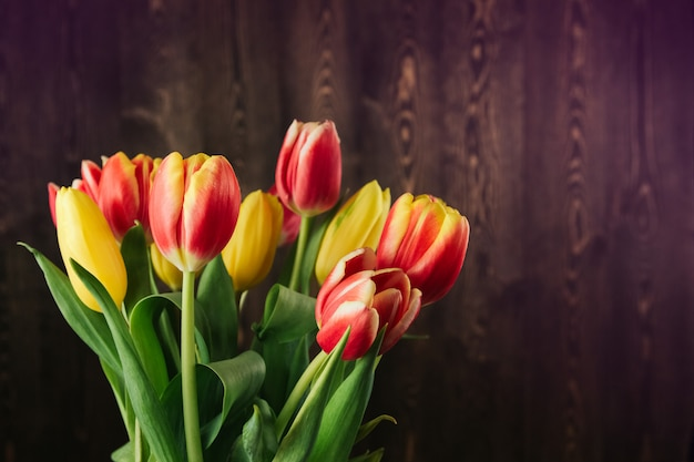 Mazzo dei tulipani rossi, gialli e rosa su uno spazio di legno marrone della copia del fondo. tulipani su un vecchio tavolo di legno piatto giaceva.