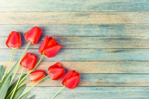Mazzo dei tulipani rossi sul retro lerciume di legno blu-chiaro con copyspace.