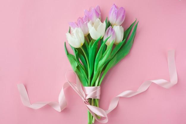 Mazzo dei tulipani su una priorità bassa pastello dentellare.