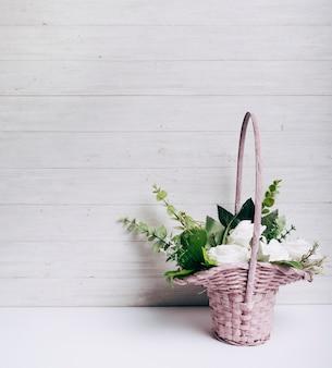 Mazzo del fiore della rosa di bianco sullo scrittorio bianco contro la parete di legno