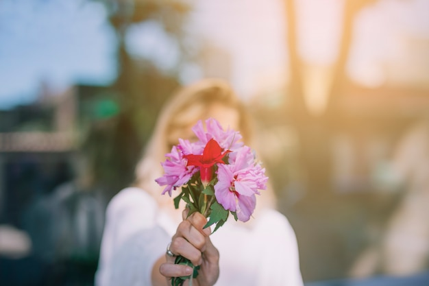 Mazzo del fiore della tenuta della giovane donna davanti al suo fronte contro il contesto vago