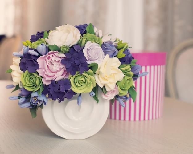Mazzo del fiore di rosa e contenitore di regalo sulla tavola di legno