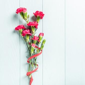Mazzo del garofano rosa sul fondo di legno del turchese leggero