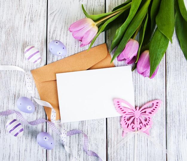 Mazzo del tulipano e carta di pasqua accogliente in bianco