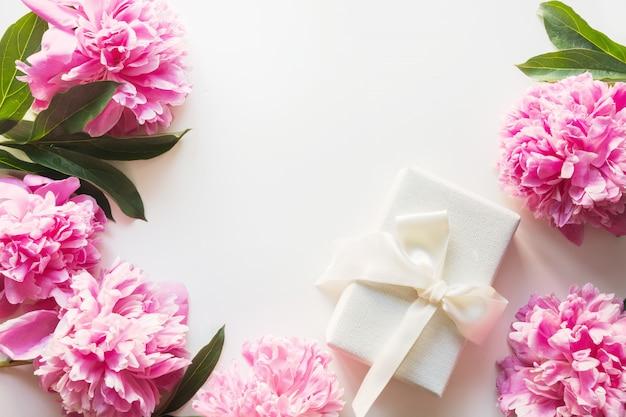 Mazzo della peonia rosa in vaso con il regalo su bianco. copia spazio per il testo. festa della mamma. vista dall'alto.