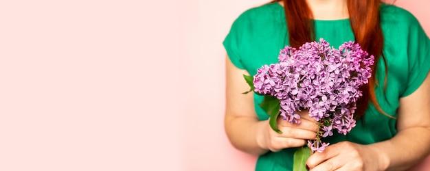Mazzo della sorgente del lillà nella mano di una ragazza su una priorità bassa dentellare