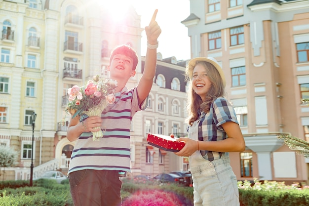 Mazzo della tenuta del ragazzo dei fiori e della ragazza con il regalo in scatola