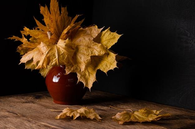Mazzo delle foglie cadute autunno in un vaso di argilla
