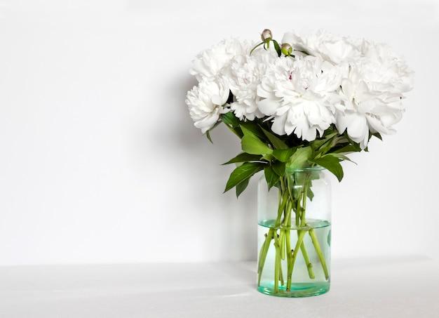 Mazzo delle peonie bianche in un vaso di vetro sul fondo bianco della parete