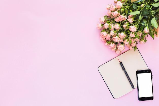 Mazzo delle rose con un diario in bianco aperto con la penna e smartphone su fondo rosa