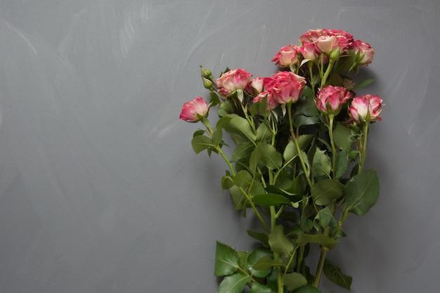 Mazzo delle rose del cespuglio macchiate rosa su gray