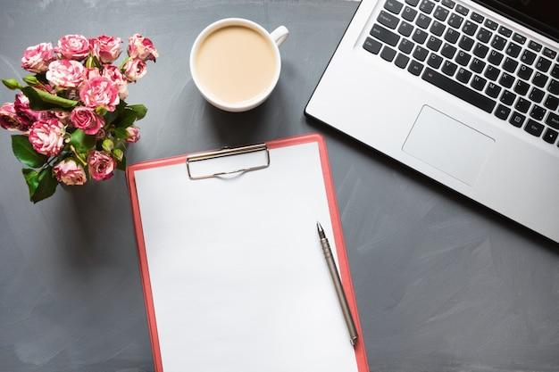 Mazzo delle rose, della tazza di caffè e del computer portatile sulla tavola grigia. vista dall'alto.