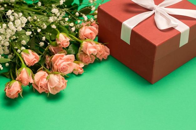 Mazzo delle rose e del contenitore di regalo rosso su fondo verde