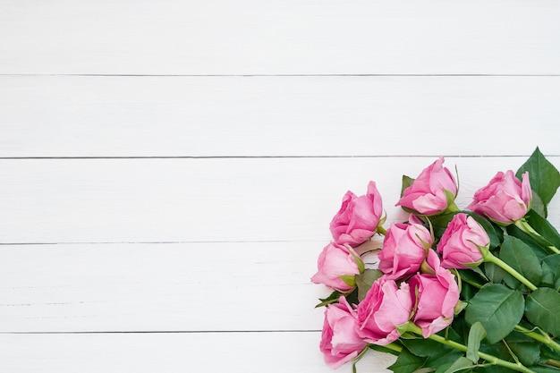 Mazzo delle rose rosa su fondo di legno bianco. vista dall'alto, copia spazio.