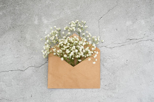 Mazzo delle rose rosa teneri con una cartolina d'auguri e una busta in bianco su fondo di legno rustico bianco