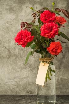Mazzo delle rose rosse nella bottiglia di vetro con l'etichetta in bianco