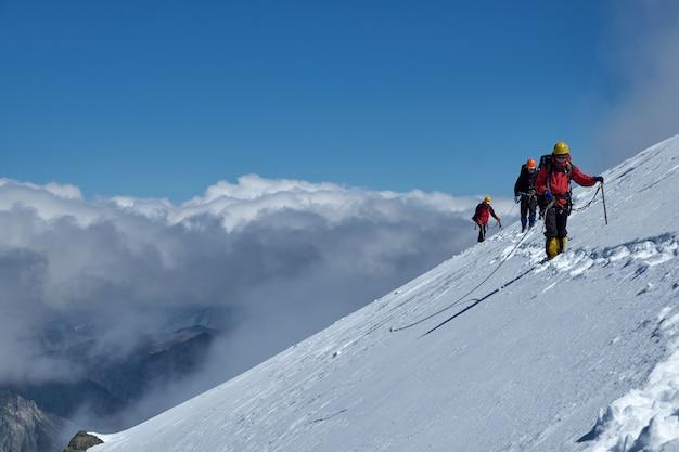 Mazzo di alpinisti si arrampica o si arrampica sulla cima di una montagna innevata