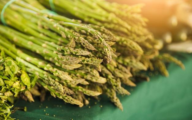 Mazzo di asparagi di giardino crudo sul tavolo in vendita