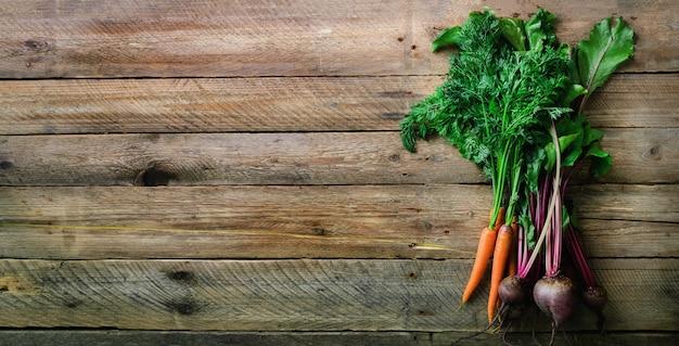 Mazzo di barbabietola e carota appena raccolte organiche con suolo e foglie, vista superiore