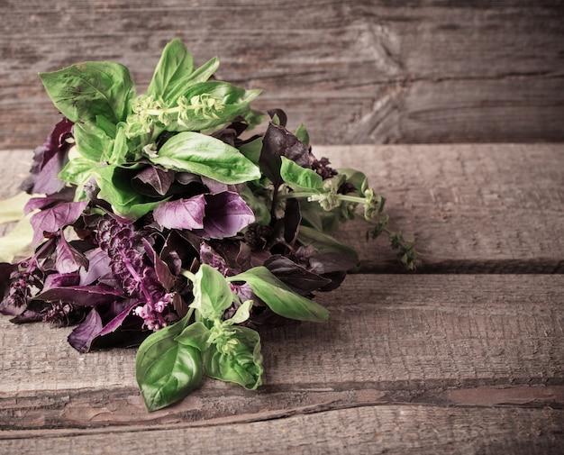 Mazzo di basilico viola e verde su una superficie di legno