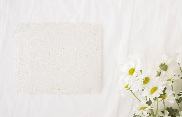 Mazzo di bei fiori sui gambi verdi vicino a carta riciclata