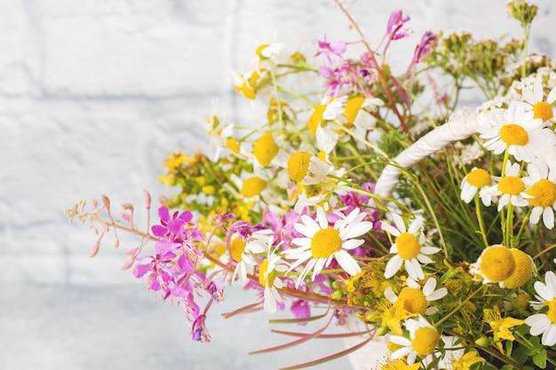 Mazzo di bei wildflowers in un cestino su una superficie grigia con lo spazio della copia.