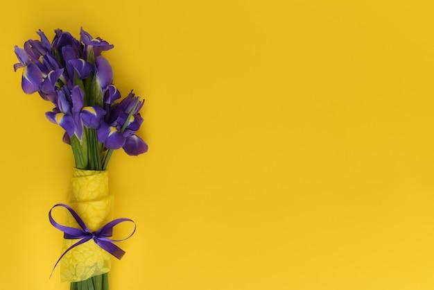 Mazzo di belle iridi primaverili su uno sfondo giallo. i fiori sono decorati con nastro giallo e viola. biglietto di auguri per la festa della donna, festa della mamma, pasqua. umore floreale. copia spazio.