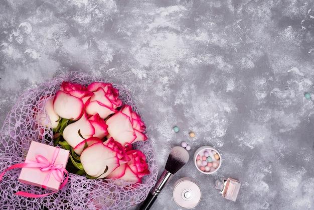 Mazzo di belle rose con cosmetici su cemento grigio