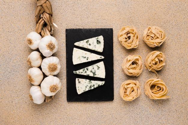 Mazzo di bulbi di aglio; fette di formaggio sul vassoio e pasta cruda disposte in fila su carta da parati in marmo