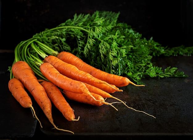 Mazzo di carote fresche con foglie verdi su sfondo scuro.