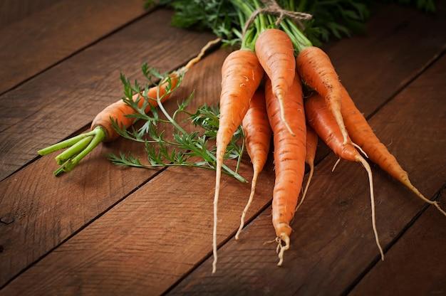 Mazzo di carote fresche con le foglie verdi sopra la tavola di legno
