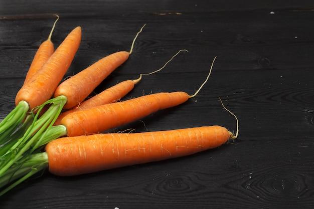 Mazzo di carote fresche con le foglie verdi sulla tavola di legno