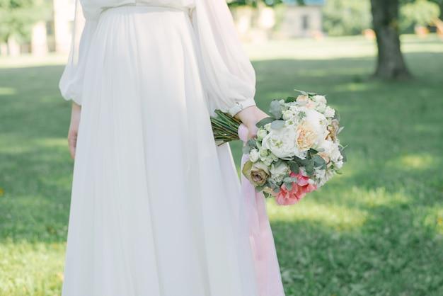Mazzo di cerimonia nuziale alla moda e bello nella mano della sposa sulla parete di erba verde