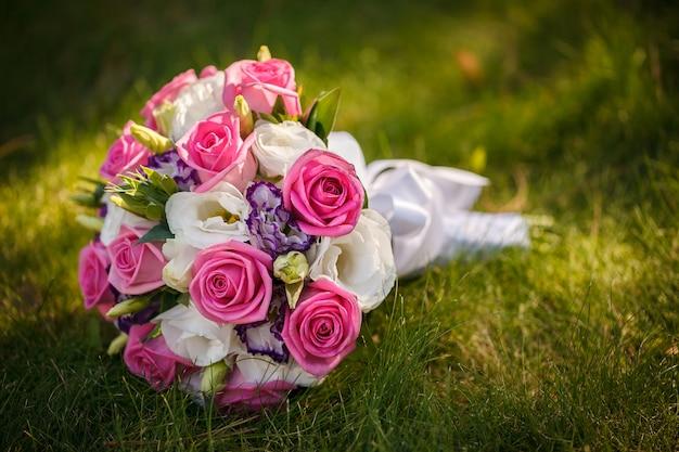 Mazzo di cerimonia nuziale dalle rose su un'erba verde