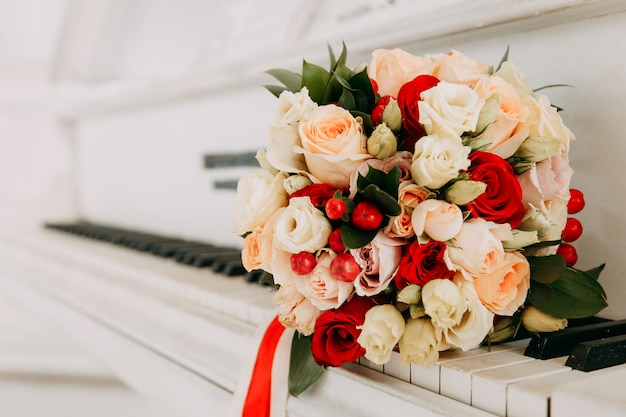 Mazzo di cerimonia nuziale dei fiori su un pianoforte a coda bianco